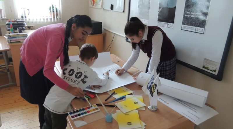 Student volunteers help children with their road safety posters